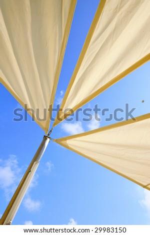Overhead awnings on a pole against blue sky - stock photo