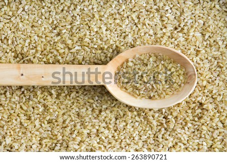 Overhead background texture of dried crushed or cracked wheat with a spoonful in a wooden spoon centered through the frame - stock photo