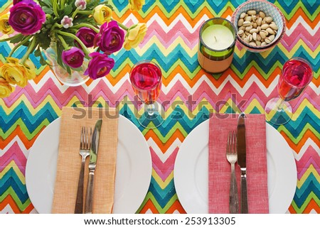 Overhead Bright colorful table setting with multi-colored chevron pattern tablecloth - stock photo