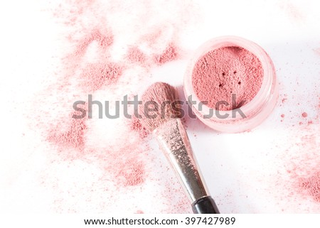 Overhead close up of one open jar of spilled pink blush powder with thick tipped brush on a white background - stock photo