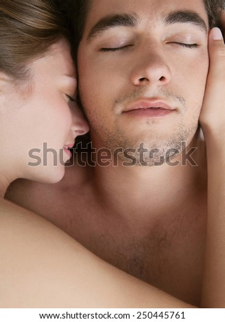 Overhead close up portrait of a young couple hugging laying down on a white bed with their heads together and their eyes closed, loving each other. Love and relationships lifestyle, interior bedroom. - stock photo