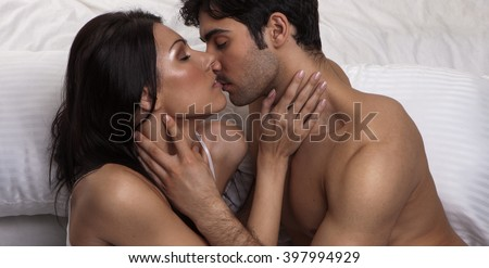 Overhead close up portrait of a young romantic couple hugging and kissing, laying down on a white bed, having sex and loving each other. Love and relationships lifestyle, interior bedroom.