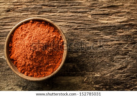Overhead close up view of a bowl of ground red cayenne pepper on a weathered heavily textured wooden background with copyspace - stock photo