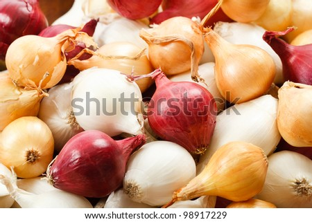 Overhead close up view of colorful red, yellow and white pearl onions - stock photo