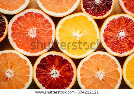 Overhead, closeup view of different color grapefruits and citrus fruit arranged artistically on a wooden table. - stock photo