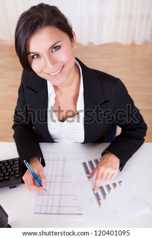 Overhead cropped image of female hands working with bar graphs and a spread sheet as she analyses data - stock photo
