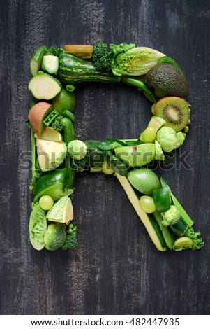 overhead flat lay display of green fruit and vegetables arranged in alphabet letter shapes, for design websites posters