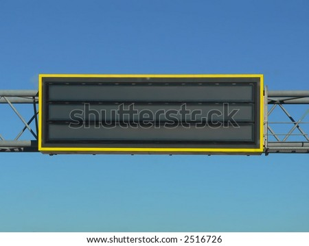 Overhead highway sign for emergency alerts like amber alerts or highway condition advisories.  The sign is blank for your own words and there is also copy space in the surrounding bright blue sky. - stock photo