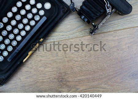 Overhead image of an old fashioned vintage typewriter with bellows camera - stock photo