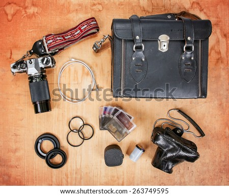 overhead image of old dirty scratched up gear needed for old school film photography enthusiasts including two cameras, a case, filters and a shutter release cable - stock photo