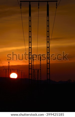 overhead line poles with wires against sunset