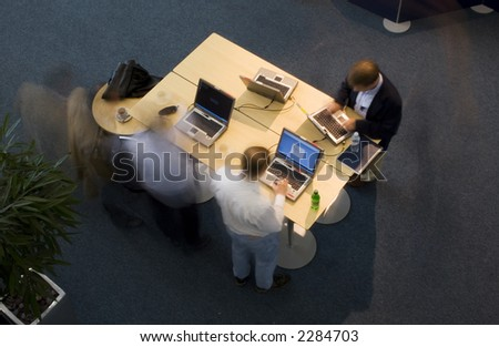 Overhead long exposure shot of executives at a conference working on laptops - stock photo