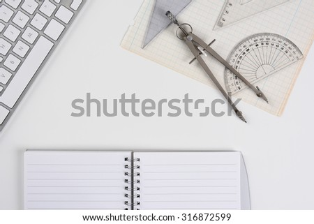 Overhead mock up of a white drafting table with computer keyboard, compass, protractor and angle open notebook and graph paper. Horizontal format with copy space. - stock photo
