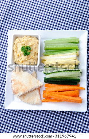 Overhead of a healthy vegetarian starter consisting of raw vegetable batons, pita bread and chickpea dip   - stock photo