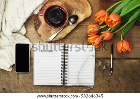 Overhead of an open book, cell phone, coffee and flowers over a wood table top ready to plan an agenda. Flat lay top view style.