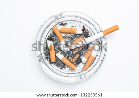 Overhead of burning cigarette in ashtray on white background - stock photo