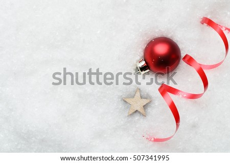 Overhead of Christmas background with decorative red bauble, ribbon swirl and wooden star partially buried in artificial white snow on the right. Copy space to the left.