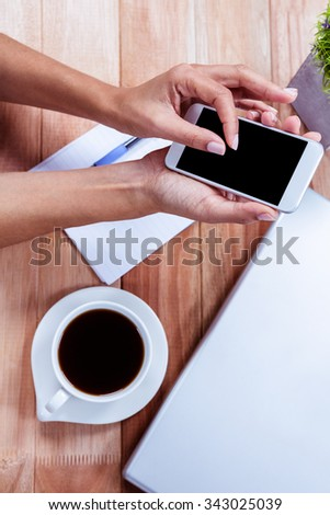 Overhead of feminine hands using smartphone and with coffee, notebook and laptop on table