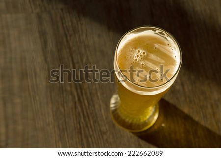 Overhead of Glass of Beer on Table in Sunlight - stock photo
