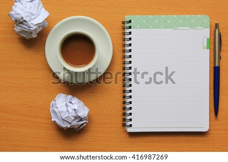 Overhead of notebook and glasses with pen and coffee cup on a desk