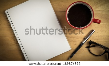 Overhead of notepad and pen and coffee on a desk - stock photo