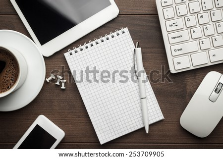 overhead of office table with notebook, computer keyboard and mouse, tablet pc and smartphone - stock photo