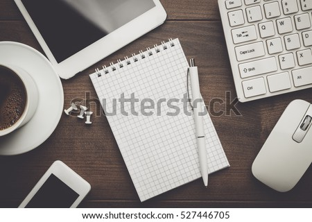 overhead of office table with notebook, computer keyboard and mouse, tablet pc and smartphone