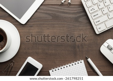 overhead of office table with notebook, computer keyboard and mouse, tablet pc and smartphone. copy space - stock photo