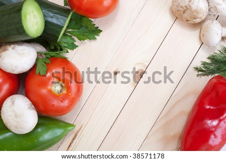 Overhead of table top with fresh veggies around the corners with empty space for text