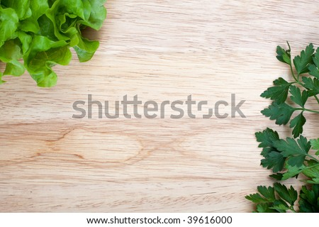 Overhead of wooden breadboard with some fresh lettuce and parsley leafs