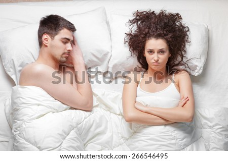 Overhead of young couple in the bed. Attractive woman is angy with her sleeping boyfriend.
