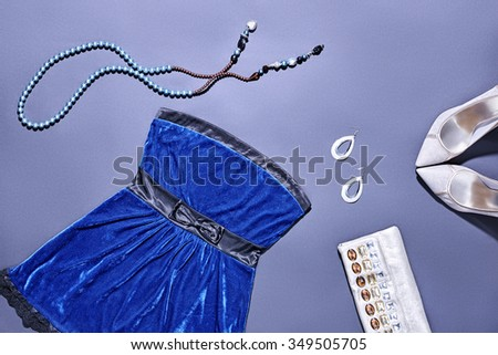 Overhead outfit Top view. Fashion clothes stylish set, blue dress and accessories. Glamor creative, trendy shiny clutch, necklace, earrings, luxury shoes heels.Unusual elegant evening party essentials - stock photo