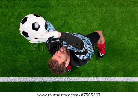 Overhead photo of a football goalkeeper jumping in the air saving the ball on the line. Focus point is on his face.