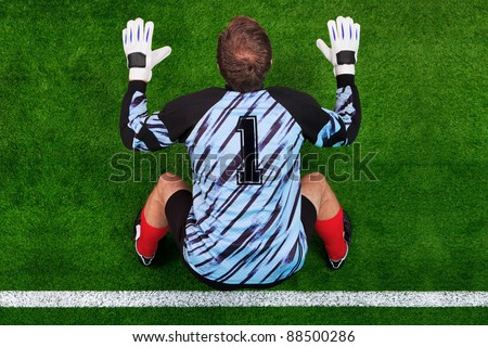 Overhead photo of a football goalkeeper standing on the goal line in ready position to face a penalty kick. - stock photo