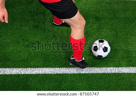 Overhead photo of a football or soccer player dribbling with the ball on the sideline - stock photo