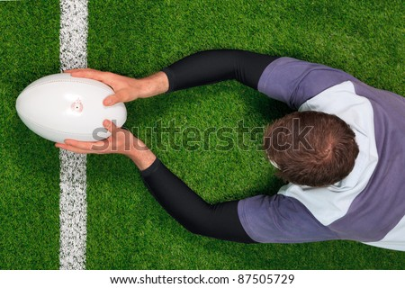 Overhead photo of a rugby player diving over the line to score a try with both hands holding the ball. - stock photo