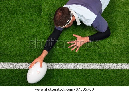Overhead photo of a rugby player stretching over the line to score a try with one hand on the ball. - stock photo