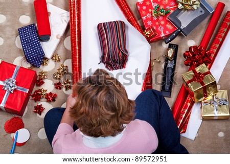 Overhead photo of a woman sat on a rug at home wrapping her Christmas presents surrounded by gifts, paper, ribbon and bows. - stock photo