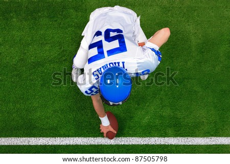 Overhead photo of an American football player center offense about to snap the ball. The uniform he's wearing is one I had made using my name and does not represent any actual team colours.