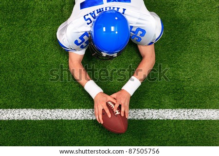 Overhead photo of an American football player making a touchdown with both hands on the ball. The uniform he's wearing is one I had made using my name and does not represent any actual team colours. - stock photo
