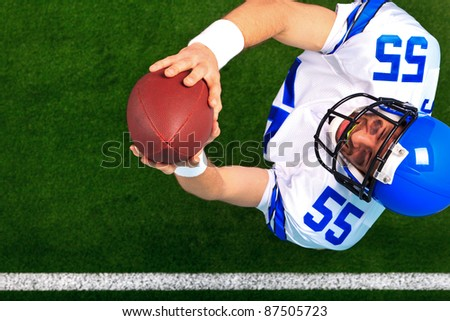 Overhead photo of an American football player wide receiver catching the ball in the air. The uniform he's wearing is one I had made using my name and does not represent any actual team colours. - stock photo