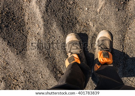 Overhead photo of feet on a background of brown sand. Man feet - stock photo