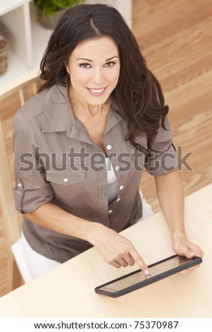 Overhead photograph of a happy beautiful young woman sitting at home using a tablet computer - stock photo
