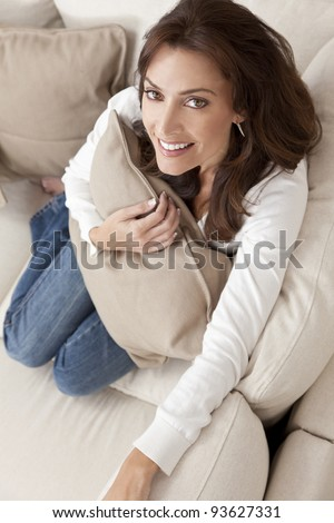 Overhead photograph of beautiful young woman at home sitting on sofa or settee holding a cushion and smiling - stock photo