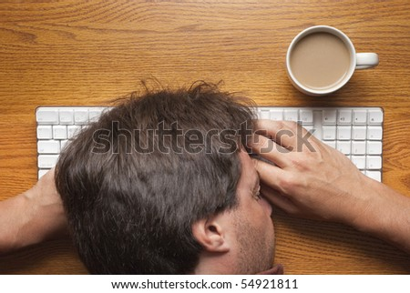 Overhead picture of a man falling asleep at computer keyboard with a cup of coffee