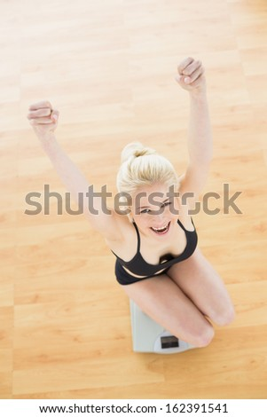 Overhead portrait of a cheerful fit woman in sportswear on scale in fitness studio - stock photo