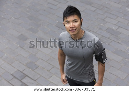 Overhead portrait of athletic Chinese man resting after urban run through city streets. Asian male runner taking break standing relaxing. - stock photo