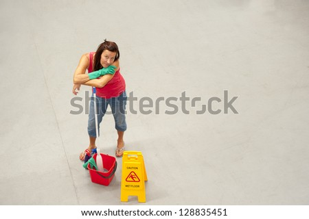 Overhead portrait of female business cleaner with mob, bucket and 'Caution Wet Floor'-Sign on warehouse floor and copy space. - stock photo