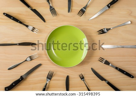 overhead shot image of greensplate surrounded with forks and knifes on wooden background - stock photo