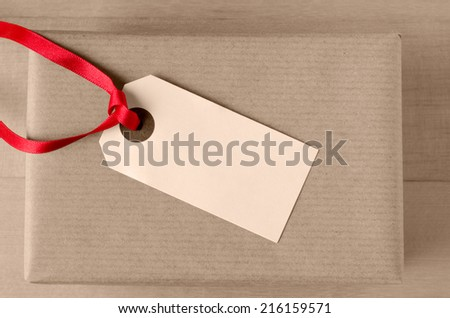 Overhead shot of a blank parcel tag, tied with red ribbon and facing upwards on top of a wrapped brown paper gift package. - stock photo